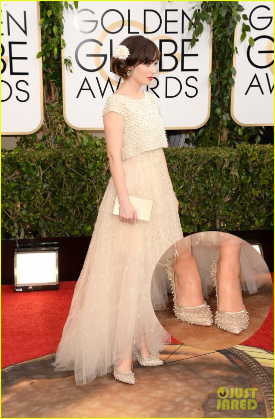 Zooey Deschanel is wearing an Oscar de la Renta ivory tulle gown and Oscar de la Renta shoes